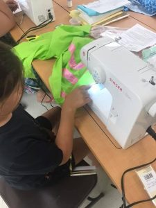 Youth sewing regalia as part of 4-H project