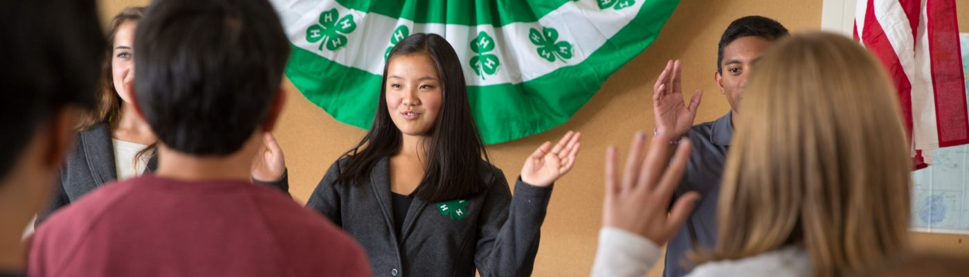 Youth reciting 4-H pledge at meeting