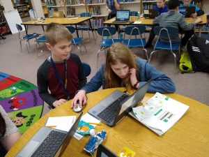 4-H members at a table completing an activity on the laptop