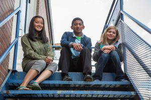 3 youth sitting on metal stairs
