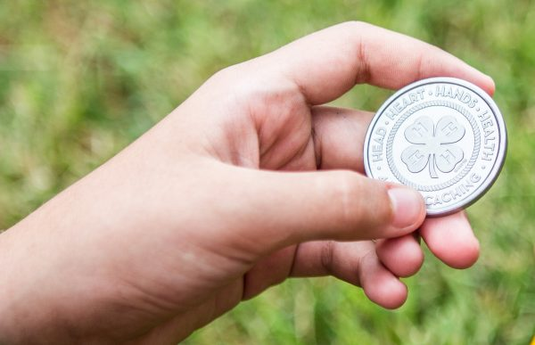 4-H member holding a coin.